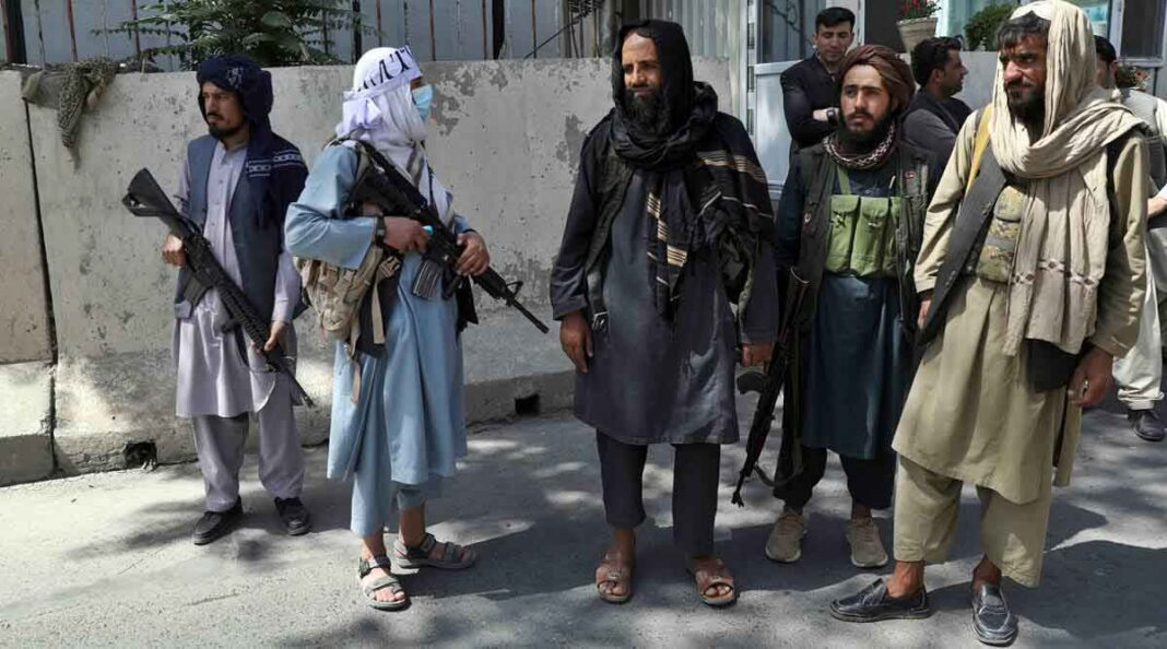 Taliban fighters stand guard at the main gate leading to the Afghan presidential palace, in Kabul, Afghanistan. (AP)