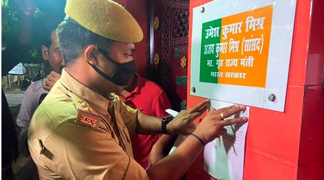 A policeman pastes a notice outside the residence of Union Minister Ajay Kumar Mishra, summoning the main accused of Tikonia violence Ashish Mishra, for his personal appearance at crime branch office on Friday at 10 am, in Lakhimpur Kheri, Thursday, Oct. 7, 2021. (PTI Photo)